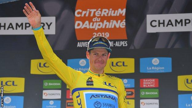 Astana rider Jakob Fuglsang waves on the podium at the 2019 Criterium du Dauphine while wearing the leader's yellow jersey