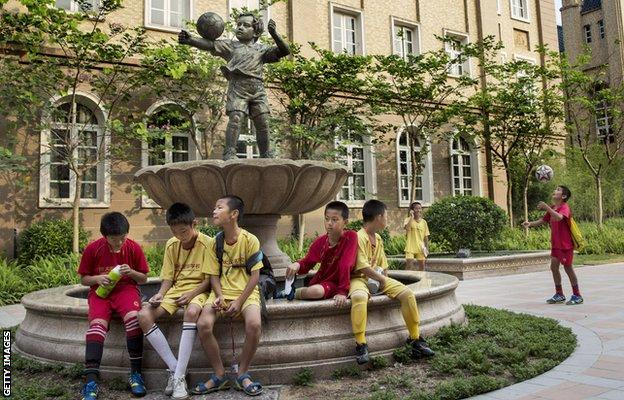 Young Chinese football players sit together in the campus as they wait to head to training at the Evergrande International Football School