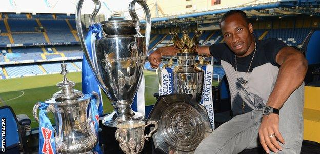Didier Drogba poses with Chelsea's trophies at Stamford Bridge