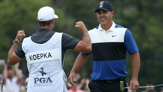 Ricky Elliott is about to embrace Brooks Koepka after the American holed the winning putt at Bethpage on Sunday