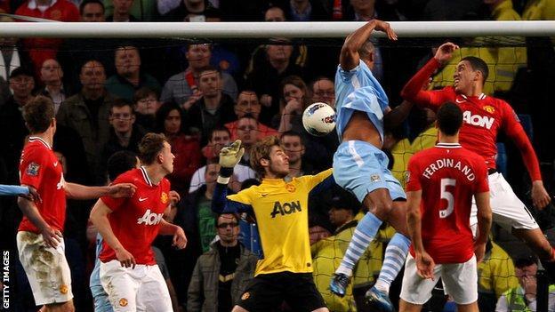 Manchester City's Vincent Kompany heads past Manchester United's David de Gea