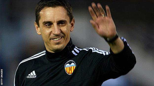 New Valencia head coach Gary Neville waves to fans at his first training session