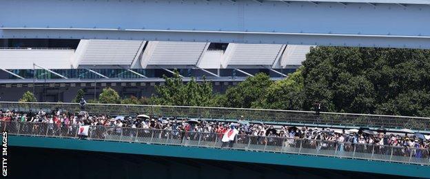 Fans watch BMX freestyle from a bridge