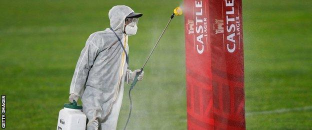 A stadium worker disinfecting pole protectors in Ellis Park