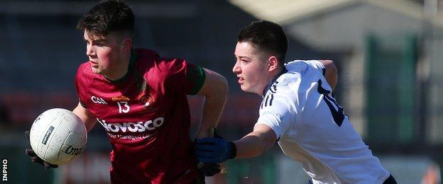 St Ronan's player Ruairi McConville with St Mary's opponent Liam Og McElhone