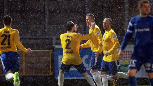 Allan Jenkins celebrates in the rain as his penalty secures a 1-0 win for Ballymena over the Mallards