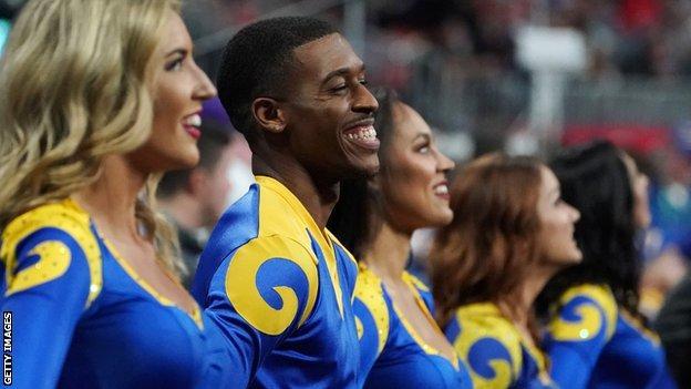 Rams cheerleader Quinton Peron smiles