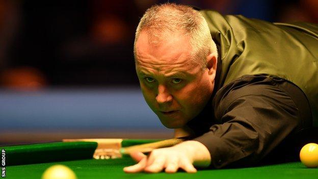 John Higgins stretching to play a shot