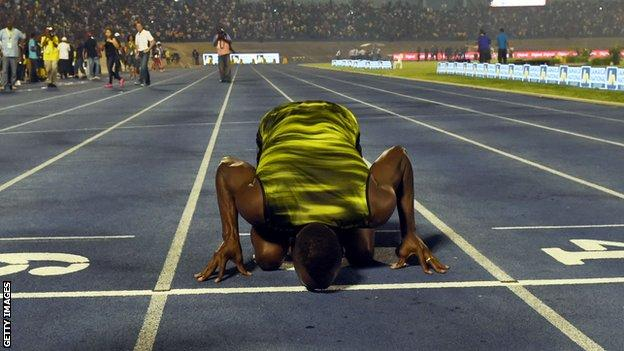 Usain Bolt kisses the track after running his last race on home soil in Jamaica