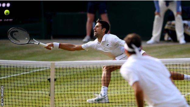 Novak Djokovic stretches for a forehand in his Wimbledon win over Roger Federer