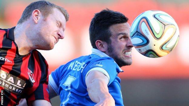David Magowan of Crusaders in action against Linfield striker Andrew Waterworth