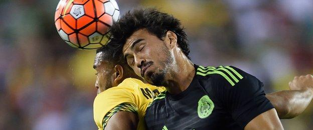 """Mexico""""s Oswaldo Alanis goes for the ball against Jamaica""""s Adrian Mariappa"""