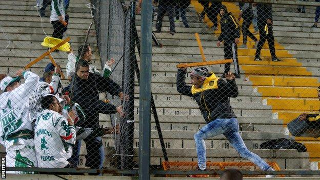 Fans of Palmeiras and Penarol fight at the end of their match.