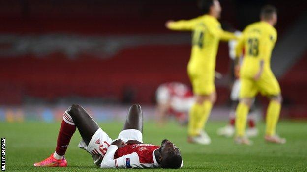 Nicolas Pepe lays on the turf as Villarreal players celebrate