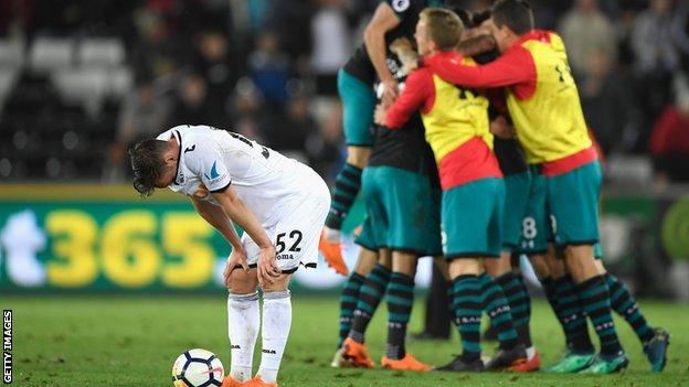 Connor Roberts bows his head in disappointment as Southampton players celebrate a season-defining victory at Swansea in May 2018