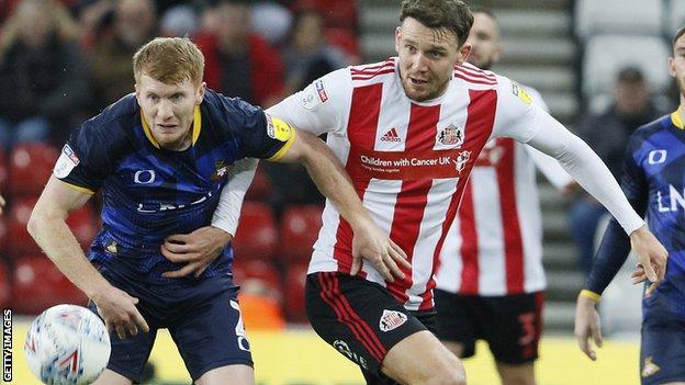 Brad Halliday of Doncaster takes on Charlie Wyke of Sunderland