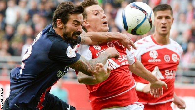 Franck Signorino of Reims challenges Paris Saint-Germain's Argentinian forward Ezequiel Lavezzi