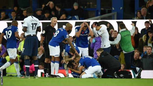 Andre Gomes is attended by medical staff as Everton and Tottenham players watch on