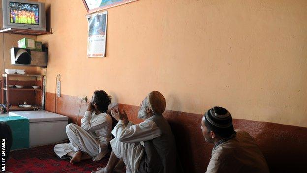 A group of Afghan men watch a match against Pakistan on a television screen in 2013