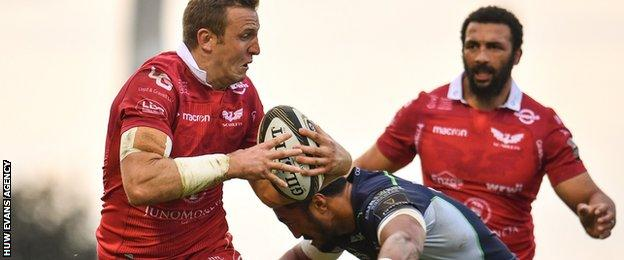 Hadleigh Parkes is tackled by Bundee Aki during a match between Scarlets and Connacht