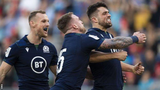 Adam Hastings celebrates scoring a try for Scotland against Italy in Rome