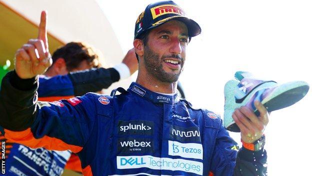 Daniel Ricciardo does a shoey on the podium at Monza