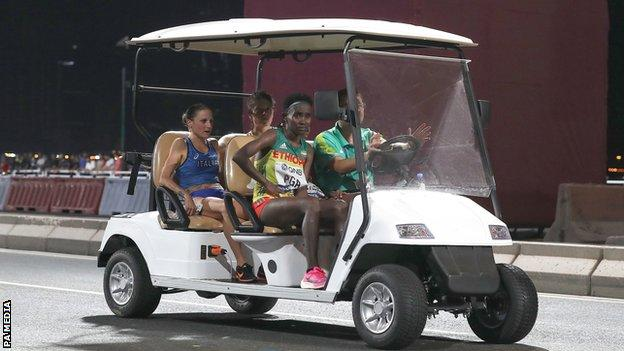 Four athletes are driven to the finish area in a kart after pulling out of the women's marathon