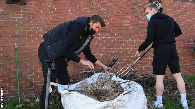 Lincoln City's Alex Palmer and Anthony Scully pitch in to help members of the Sincil Community Land Trust regenerate a garden