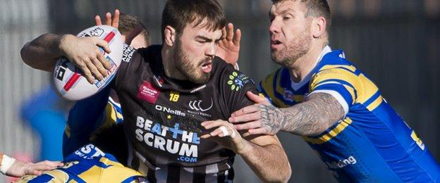 Widnes' James Chapelhow is tackled against Leeds