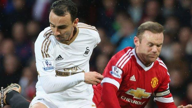 Leon Britton is challenged by Wayne Rooney