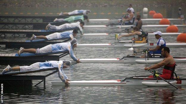 Volunteers hold boats ahead of the men's sculls race, Beijing Paralympics 2008
