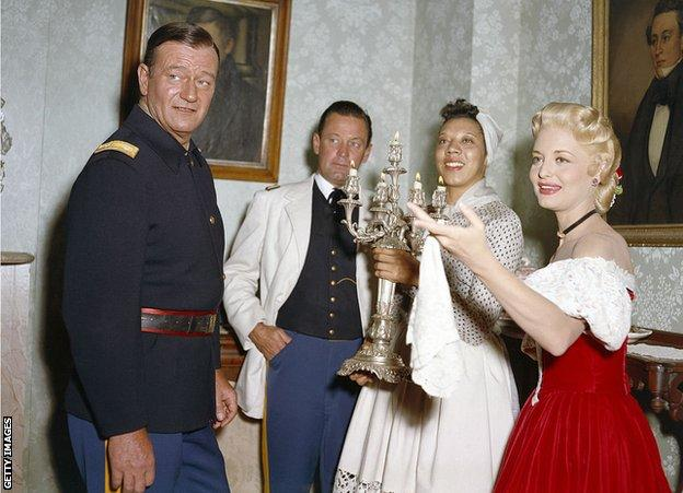 American actors John Wayne, William Holden, Althea Gibson and Constance Towers on the set of The Horse Soldier, directed by John Ford