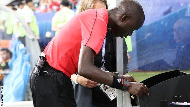 Gambian referee Bakary Papa Gassama using VAR technology