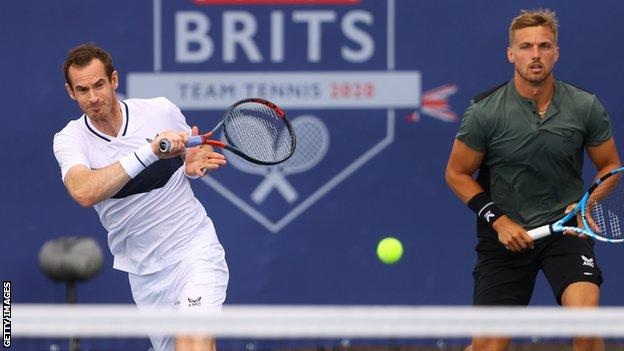 Andy Murray hits a return as Lloyd Glasspool watches on in the Battle of the Brits
