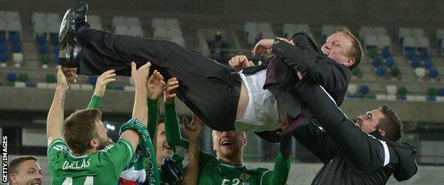 Northern Ireland manager Michael O'Neill is thrown in to the air by players