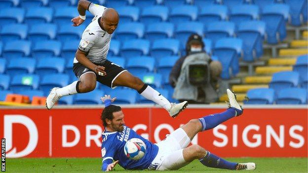 Cardiff captain Sean Morrison makes a sliding challenge on Swansea's Andre Ayew