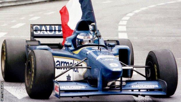 Olivier Panis waves a French flag while in the Ligier car after winning the Monaco GP in 1996