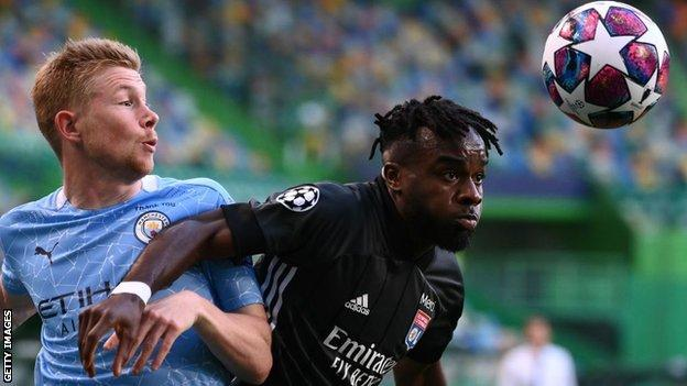 Maxwel Cornet challenges Manchester City's Kevin de Bruyne for the ball