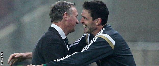 Michael O'Neill embraces Kyle Lafferty after Northern Ireland's qualifier win in Greece