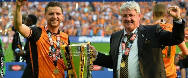 Steve Bruce holds the Championship Play-off Final Trophy aloft with his son, centre-half Alex Bruce