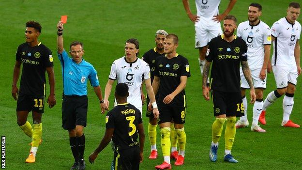 Rico Henry is shown a red card against Swansea