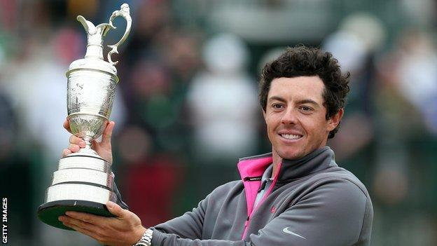 Rory McIlroy holds aloft the Claret Jug