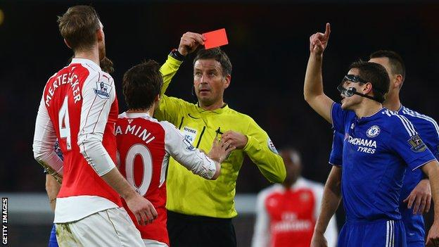 Mark Clattenburg shows Per Mertesacker a red card