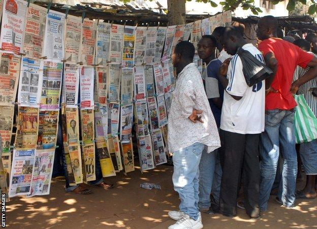 Residents of Togo's capital Lome read through newspaper reports of the attack