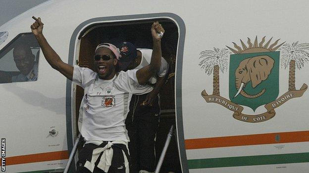 Didier Drogba emerges from the plane that took the victorious Ivory Coast team back home from Sudan