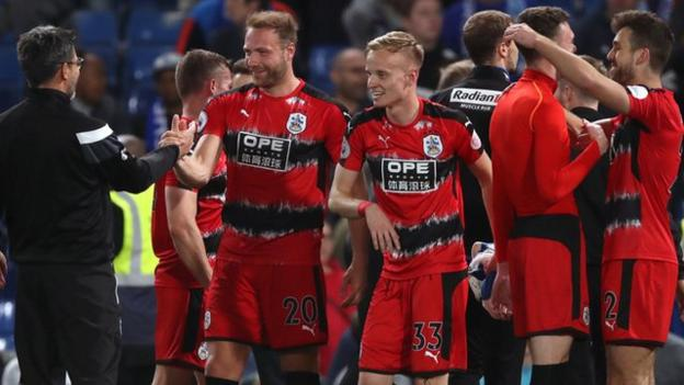 Huddersfield's players and management celebrate after securing Premier League safety