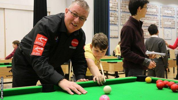 A young snooker player being coached.