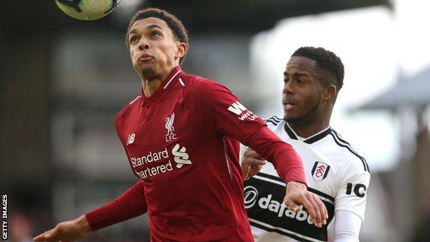 Liverpool defender Trent Alexander-Arnold heads the ball under pressure from Fulham's Ryan Sessegnon