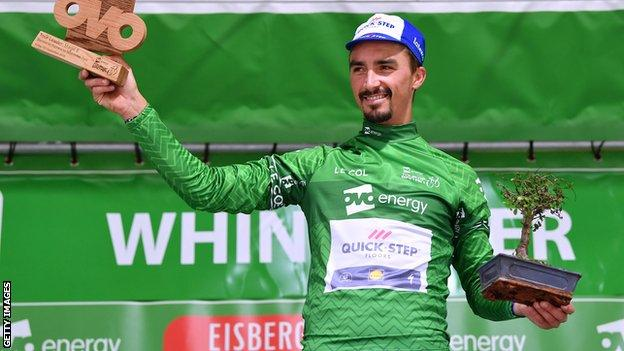 Julian Alaphilippe on the podium in the leader's green jersey