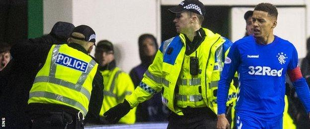A fan is led away by police after confronting Rangers' James Tavernier